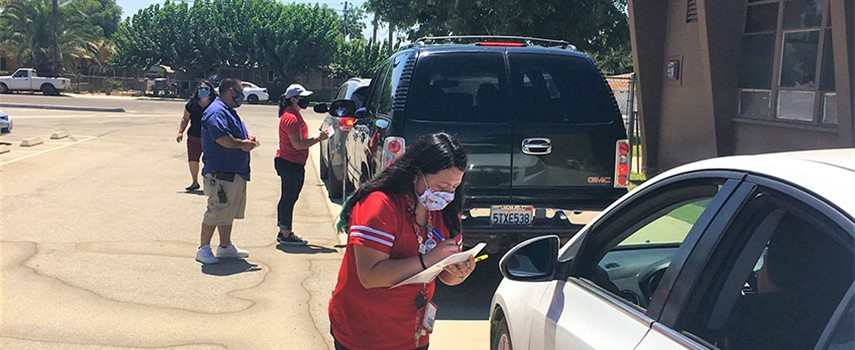 Staff assist families picking up student materials at their drive through distribution.